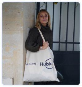 Jeune femme posant devant son domicile avec sac en tissu du pressing à domicile Hublo